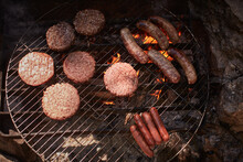 Burgers And Sausages Cooking On Campfire