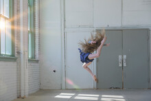 Teenage Girl With Long Brown Hair Leaping Mid Air In Dance Studio