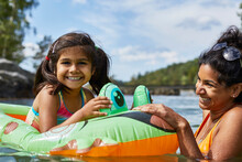 Mother Playing With Daughter On Inflatable Frog In Lake