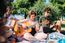 Group Of Friends Relaxing, Playing Guitar At Picnic In Park