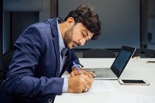 Businessman Writing Notes And Using Laptop In Office