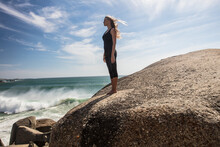 Young Woman Practicing Yoga Taking A Break Looking Out From Beach Boulder, Cape Town, Western Cape, South Africa