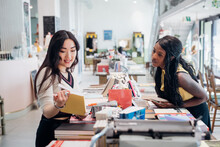 Young Businesswomen Browsing Book In Bookshop