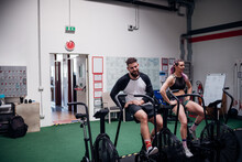 Exhausted Young Woman And Man Training Together On Gym Exercise Bikes, Taking A Break