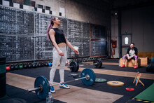 Young Man Watching Woman Preparing To Lift Barbell In Gym