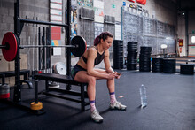 Young Woman Training, Sitting On Weights Bench In Gym Looking At Smartphone