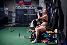 Young Woman Training, Sitting On Bench Drinking Bottled Water In Gym