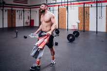 Bare Chested Young Man Training, Holding Bottled Water And Towel In Gym, Full Length