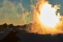 Sun Behind Veil Of Clouds Over Mountain Range, Saas-Fee, Valais, Switzerland