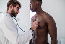 Doctor Examining Patient In Consultation Room