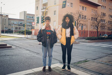Two Cool Young Women Standing By City Tramline