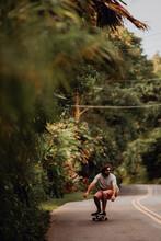 Mid Adult Male Skateboarder Crouching While Skateboarding Along Rural Road, Haiku, Hawaii, USA