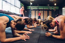 Women Training In Gym With Male Trainers, Doing Push Ups