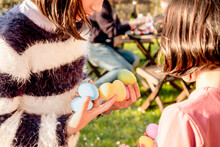 Two Girl With Handfuls Of Dyed Easter Eggs At Table, Cropped
