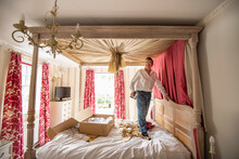 Curtain Fitter Putting New Drapes On Four Poster Bed