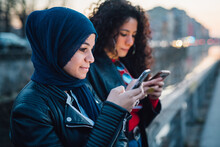 Young Woman In Hijab With Best Friend Looking At Smartphones By City Canal