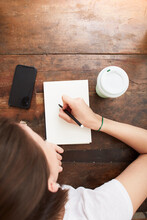 Woman Writing On Notebook At Coffee Break