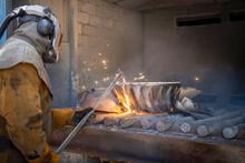 Worker Cutting Up Scrap Titanium Aircraft Parts In Titanium Recycling Plant