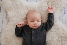 Baby Boy Sleeping On Sheepskin Rug In Crib, Overhead View