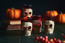Close Up Of Human Skull Candles And Orange Pumpkins On A Table.