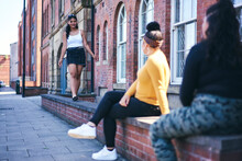 Young Woman Walking Along Wall Watched By Teenage Sisters