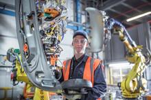 Portrait Of Apprentice Engineer Programming Robots In Car Factory