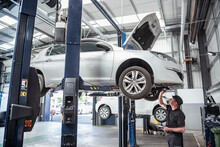 Engineer Checking Car On Ramp In Car Service Centre