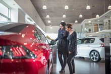 Saleswoman And Customer Inspecting New Car In Car Showroom