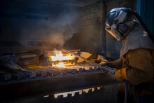 Worker Cutting Up Scrap Titanium Aircraft Parts In Titanium Recycling Plant