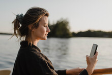 Woman Using Smartphone By Lake, Bobcaygeon, Ontario, Canada