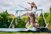 Girl Playing With Soap Bubbles, Sister In Background With Diabolo