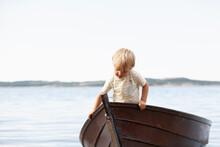 Boy Playing In Boat On Beach