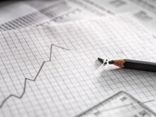 A Graph Illustrating Business Data, A Line On A Chart Rising And Dipping And A Broken Lead Pencil.