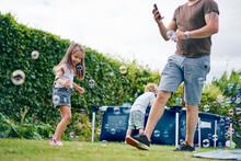 Father Walking Past Children Playing In Garden