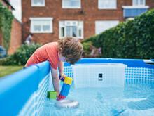 Boy Filling Up Water Gun From Pool Water