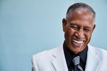 Portrait Of Senior Businessman Laughing, Blue Background
