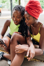 Friends Reading Text Message On Smartphone In City