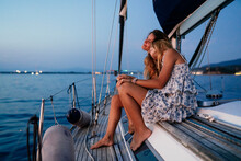 Close Friends Relaxing On Sailboat In Evening, Italy