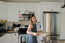 Laughing Woman Carrying Cutting Board In Kitchen