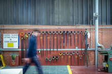 Worker Walking Passed Lifting Hooks In Steelworks