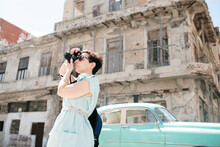 Woman Traveller Taking Photograph In City, Cuba