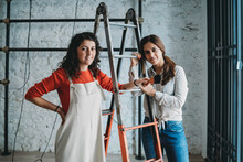 Two Mid Adult Women Leaning On Step Ladders With Paint Brush In Their New Shop, Portrait