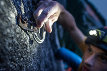 A Man Trad Climbing At Night Hooking A Caribiner Onto A Clip On Squamish, British Columbia, Canada