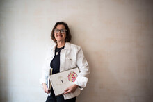 Portrait Of Brunette Woman Wearing Glasses And White Denim Jacket, Holding Artist's Sketch Books.
