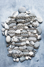 Grey And White Pebbles In An Oval Shape With Silver Metal Chains Lying Across Them In Bands.