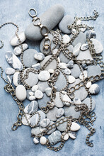 Grey And White Pebbles On A Grey Background With Silver Metal Chains Lying Amongst Them.