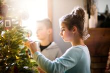 Siblings Decorating Christmas Tree At Home