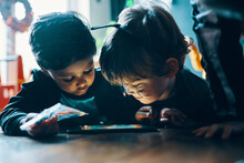 Two Children Standing Next To A Table Looking At A Computer Tablet.