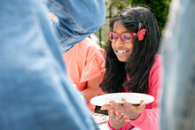 Young Girl With Plate At Outdoor Family Lunch, Florence, Italy