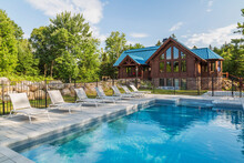 In-ground Salt Water Swimming Pool And Brown Stained Milled Eastern White Pine Timber And Flat Log Profile Home Facade With Stone Cladding On Walk-out Lower Level And Blue Standing-seam Sheet Metal Roof, Quebec, Canada